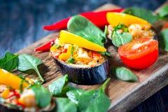 Baked充塞了茄子用胡椒、乳酪和蕃茄在土气木桌,素食食物上 免版税库存照片