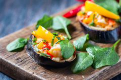 Baked充塞了茄子用胡椒、乳酪和蕃茄在土气木桌,素食食物上 库存图片