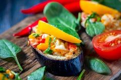 Baked充塞了茄子用胡椒、乳酪和蕃茄在土气木桌,素食食物上 免版税图库摄影