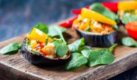 Baked充塞了茄子用胡椒、乳酪和蕃茄在土气木桌,素食食物上 免版税库存图片