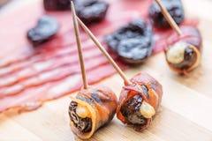 Baked烘干了李子充满乳酪,并且烟肉滚动了,快餐或开胃菜 免版税库存图片