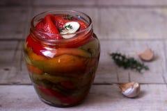 Baked腌制了甜椒用大蒜和麝香草在一个玻璃瓶子 库存照片