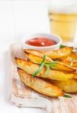 Baked зажарило картошки с красными соусом и пивом на белой предпосылке, селективном фокусе Стоковое Изображение