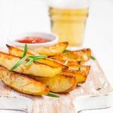 Baked зажарило картошки с розмариновым маслом и томатным соусом на белой предпосылке, селективным фокусом Стоковые Изображения