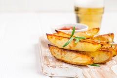 Baked зажарило картошки с розмариновым маслом и томатным соусом на белой предпосылке, селективным фокусом Стоковая Фотография