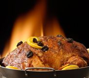 Baked. Ham with raisins on top and fire wood oven in the background Stock Image