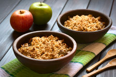 Baked Apple Crumble or Crisp. Two rustic bowls of baked apple crumble or crisp on kitchen towel, wooden spoons and fresh apples on the side, photographed on dark stock images