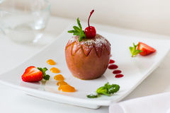 Baked apple with fruit jam on plate Stock Photos