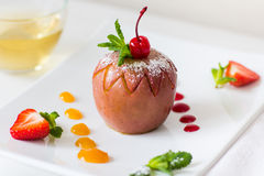 Baked apple with fruit jam on plate Stock Image