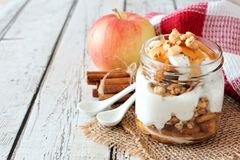 Baked apple parfait in a mason jar on white wood Royalty Free Stock Photos