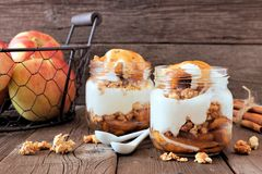 Baked apple parfaits with caramel in mason jars on rustic wood Stock Photo