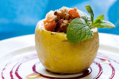 Baked apple stuffed nuts pumpkin honey, sweet redberry sause and seasoned green mint leaf. Stock Photo