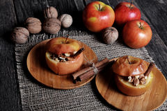 Baked apple with sugar and nuts. Selective focus Stock Image