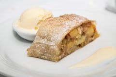 Baked Apple Tart with Vanilla Ice Cream and Sauce. An apple tart pastry on a white plate with vanilla ice cream Stock Images