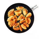 Baked apples with cinnamon on a frying pan. Apples baked with cinnamon on a frying pan isolated on white Royalty Free Stock Image