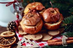 Baked apples with cinnamon on rustic background. Autumn or winter dessert. Closeup photo of a tasty baked apples with christmas de Stock Photography