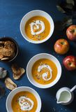 Baked apples and pumpkin soup with sage butter on blue table a top view. Seasonal comfort food royalty free stock photography