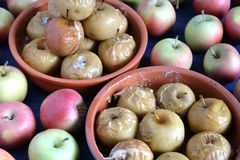Baked apples in round clay dishware and lot lot of ripe fresh apples on blue tablecloth around stock image