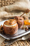 Baked apples stuffed with dried fruit, nuts and cottage cheese, honey, cinnamon. Close-up, horizontal. Royalty Free Stock Image