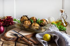 Baked artichokes stuffed with meat, mushrooms and mint, italian cusine. Baked artichokes cooked with meat, mushrooms, italian cusine Top view stock image