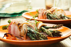 Baked asparagus wrapped in chicken and bacon Stock Image