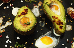 Baked avocado with quail egg, black salt and pepper Stock Photo