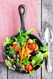 Baked baby carrots, beetroot, cherry tomatoes, pearl onion and garlic in a pan with fresh chard, salad leaves, chive and curly par. Sley, on a wooden table. Top royalty free stock image