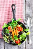 Baked baby carrots, beetroot, cherry tomatoes, pearl onion and garlic in a pan with fresh chard, salad leaves, chive and curly par. Sley, on a wooden table. Top stock photo