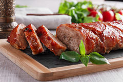 Baked bacon wrapped meatloaf with salad Stock Photo