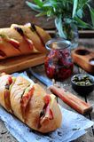 Baked baguette stuffed with bacon, cheese, sun-dried tomatoes and capers Stock Photo