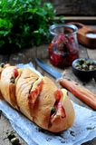 Baked baguette stuffed with bacon, cheese, sun-dried tomatoes and capers Stock Photos