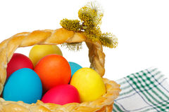 Baked basket with Easter colored eggs Royalty Free Stock Images
