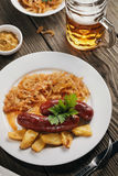 Baked Bavarian sausages with stewed cabbage and a glass of beer Royalty Free Stock Photo