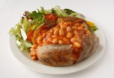 Baked Bean Jacket Potato with side salad. A baked bean baked potato on a plate with side salad Royalty Free Stock Photo