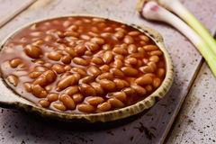 Baked beans. Closeup of an earthenware bowl full of baked beans and some green garlics on a rustic wooden table Stock Image