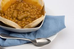 Baked beans with English muffin. In a Bowl with Blue Cloth and spoon Royalty Free Stock Photo