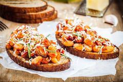 Baked beans with rosemary and parmesan on toast Royalty Free Stock Image