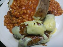 Sausages with cheese and jacket potato. Baked beans on the side Royalty Free Stock Image