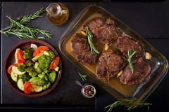 Baked beef steak with garlic and rosemary and vegetables. Royalty Free Stock Image