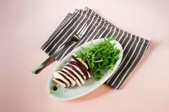 Beetroot and cheese on skewer,rucola leaf. Baked beetroot and white cheese on skewer and fresh rucola leaf on white plate, striped dishtowel on pink background Royalty Free Stock Photo