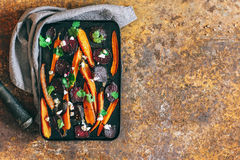 Baked beets and carrots in a vintage black pan royalty free stock image