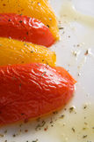 Baked bell pepper. Halves of yellow and red sweet peppers on white plate with olive oli based dressing stock image
