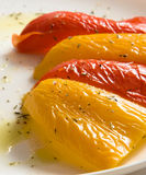 Baked bell pepper. Halves of yellow and red sweet peppers on white plate with olive oli based dressing stock images