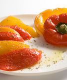 Baked bell pepper salad. Halves of yellow and red sweet peppers on white plate with olive oli based dressing stock image
