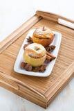 Baked a bourré des pommes d'un plat blanc sur le plateau en bois Photos stock