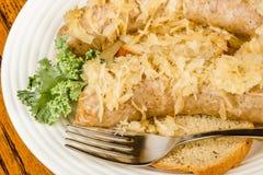Baked bratwurst with sauerkraut. On rye bread Stock Photo