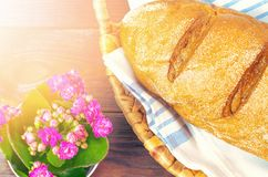 Baked bread in braided basket on a wooden table a sunny day. stock photos