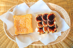 Baked bread buttered and bread chocolate on bamboo plate. Royalty Free Stock Photos