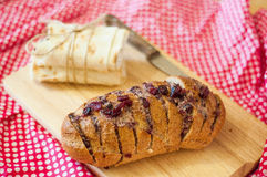Baked bread with cheese and dried cherries. On wooden board and dotted napkin around Stock Photography
