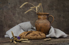 Baked bread, crock and spikelets on wooden boards stock photography